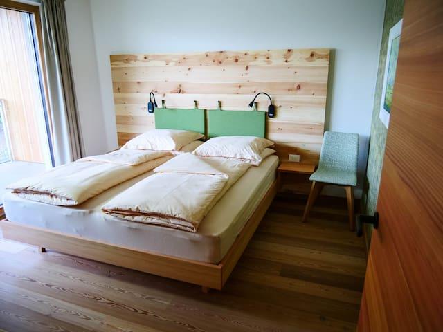 Blick in das Schlafzimmer mit der Zirbenholzrückwand