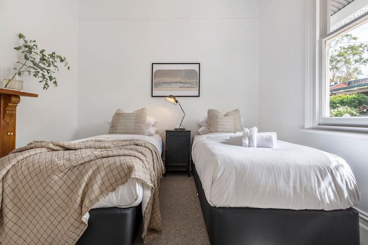 The third bedroom with two single beds boasts a classic fireplace that adds a bit character to the space.