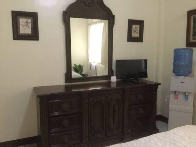 Dresser and water dispenser in room.