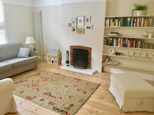 Lounge, with 3 person sofa, armchair, footstool containing lots of toys, real fire