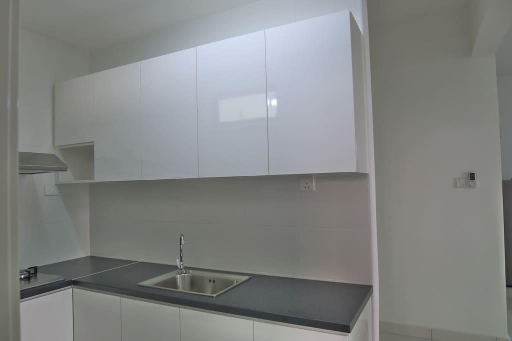 Kitchen cabinet with sink. Gas stove is at left.