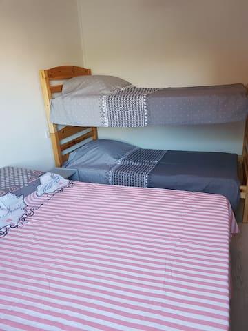 une des 2 chambres avec un lit double et lit superposé et sur le côté une armoire de rangement avec penderie
