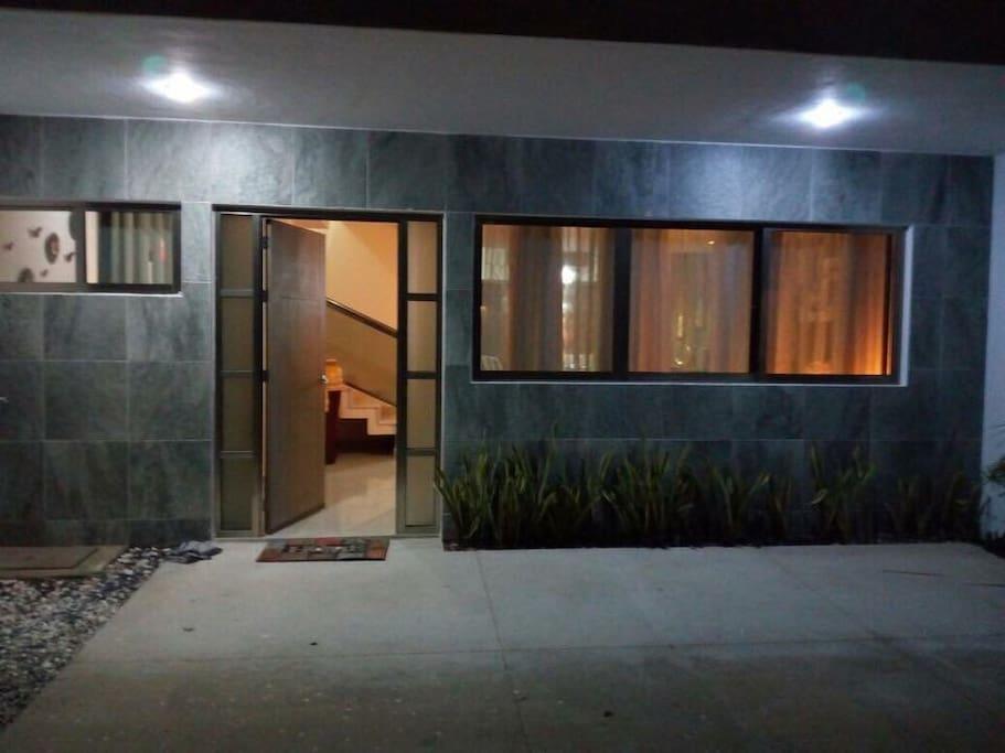 Entrada de la casa con luz y el estacionamiento privado