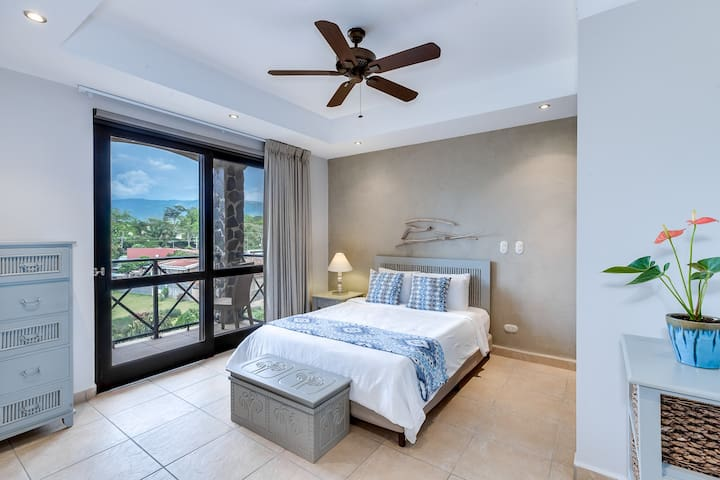 Second bedroom with queen size bed and balcony access.