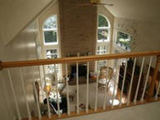 Balcony from the second floor overlooking the family room. There is a wood burning fireplace in the family room.