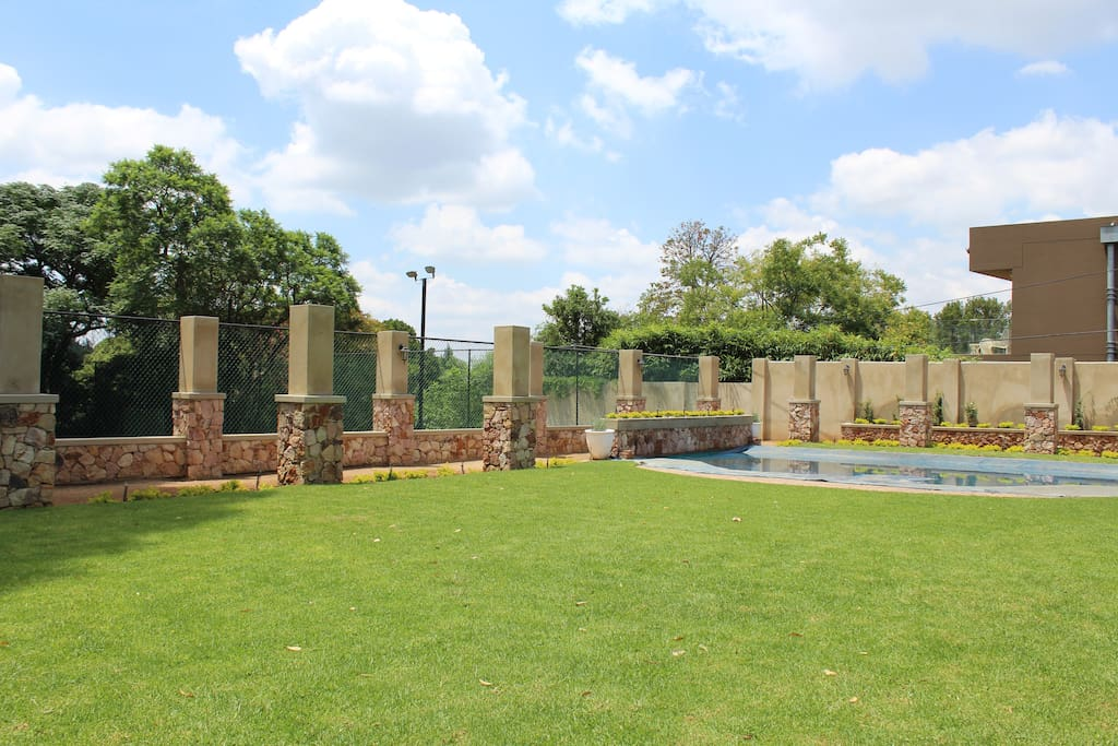 Lush green garden surrounds sparkling  swimming pool