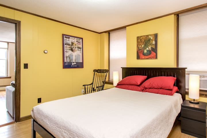 "The ""Yellow Bedroom"" with queen sized bed, dresser, flat screen TV, and walk-in closet"
