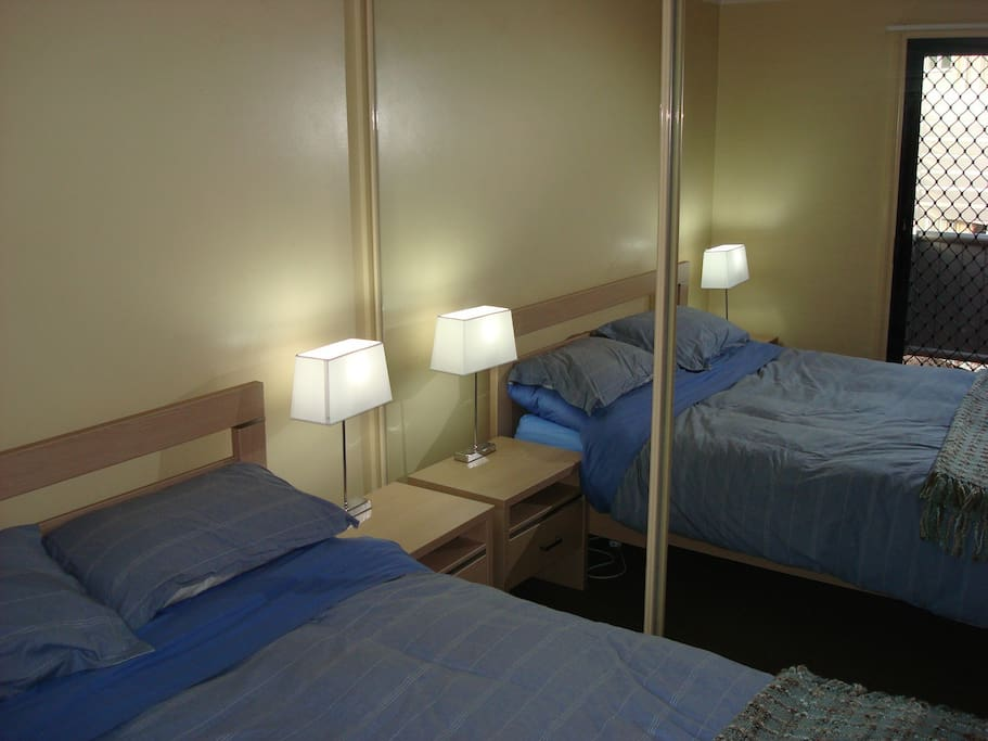 2 bedrooms both with Queen beds with pillows comforted sheets blanket table lamps and mirrored wardrobe. access to balcony