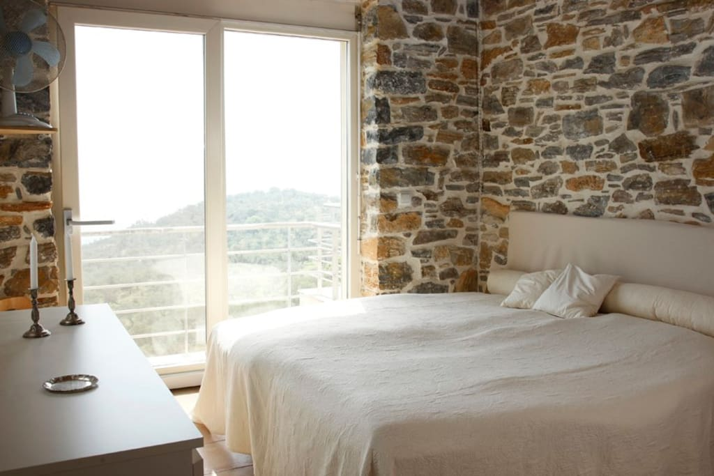 Master bedroom with balcony overlooking olive orchard and Aegean Sea