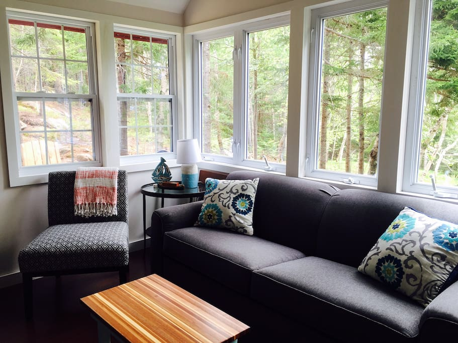 A bright and cozy living room with views of the woods all around you. The couch pulls out to a very comfortable sofa bed.