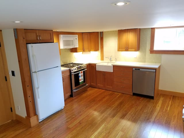 Fully furnished kitchen with brand new gas range, microwave and dishwasher. Custom reclaimed old growth fir cabinets and custom tile backsplash.