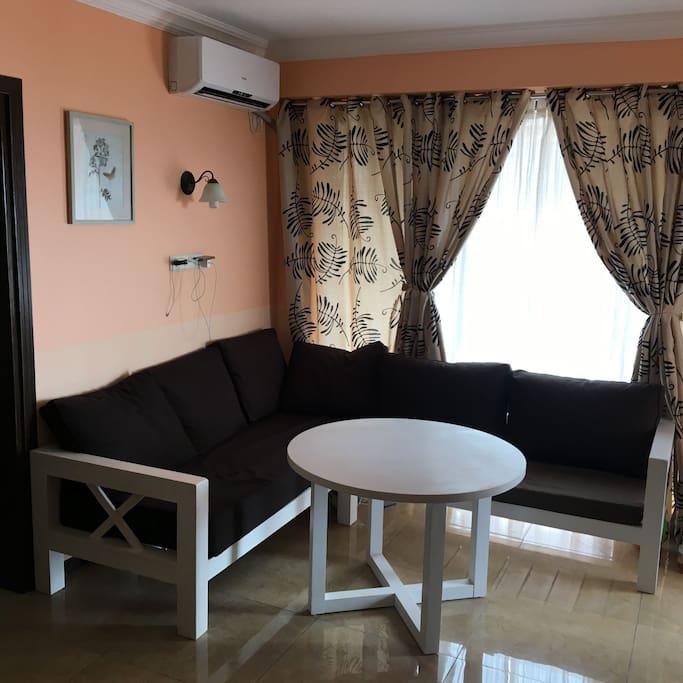 гостиная комната с угловым диваном и телевизором и кухней