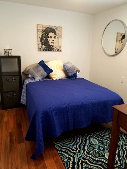 Full size bed with 4 pillows and a writing desk.