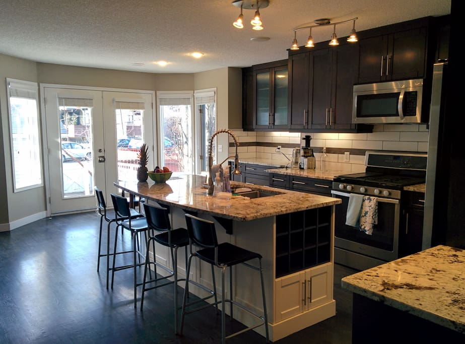 Kitchen features a large granite island, soft-close cabinets, stainless steel appliances, and corner pantry