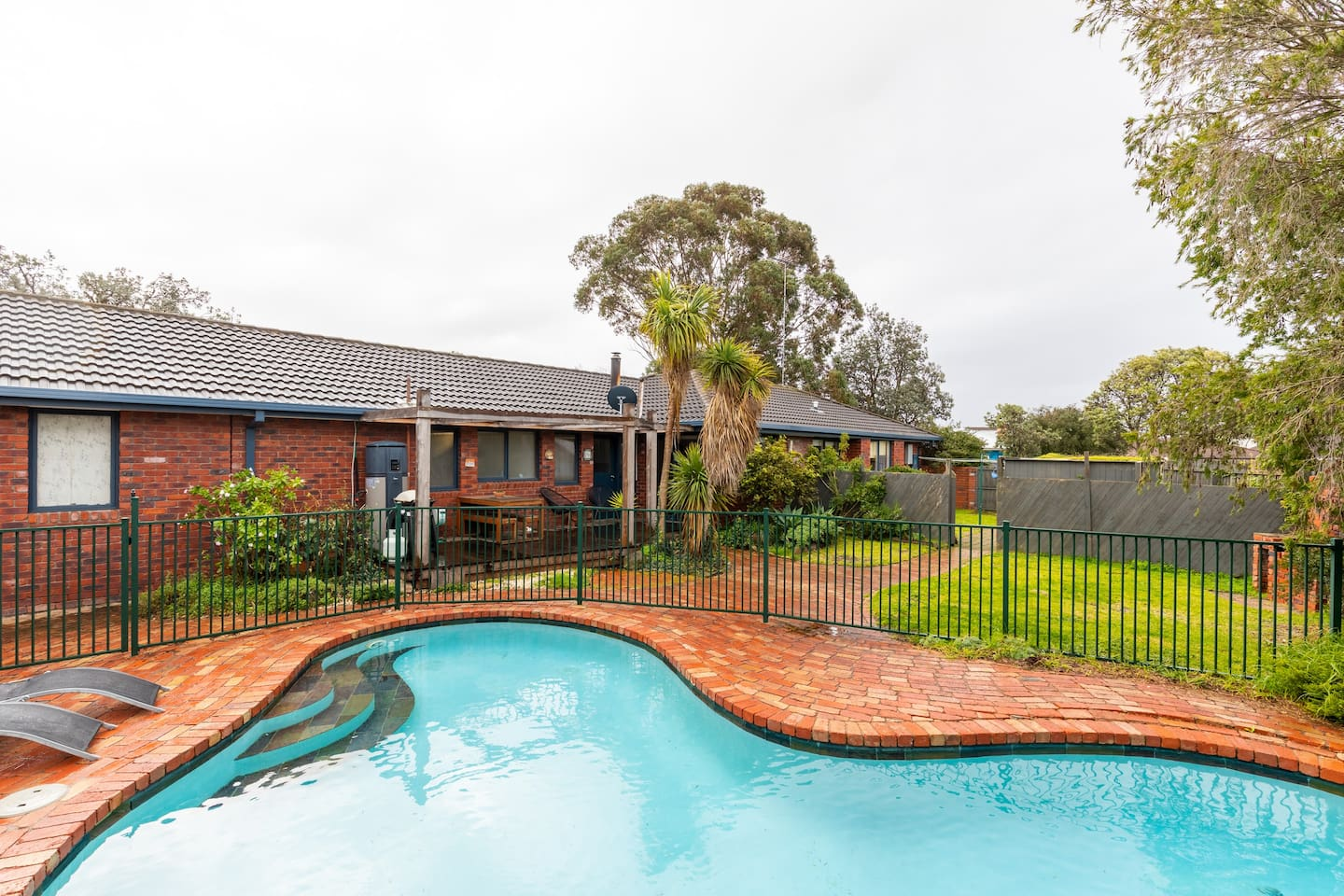 Spacious back yard with safely fenced pool and entertainer's deck