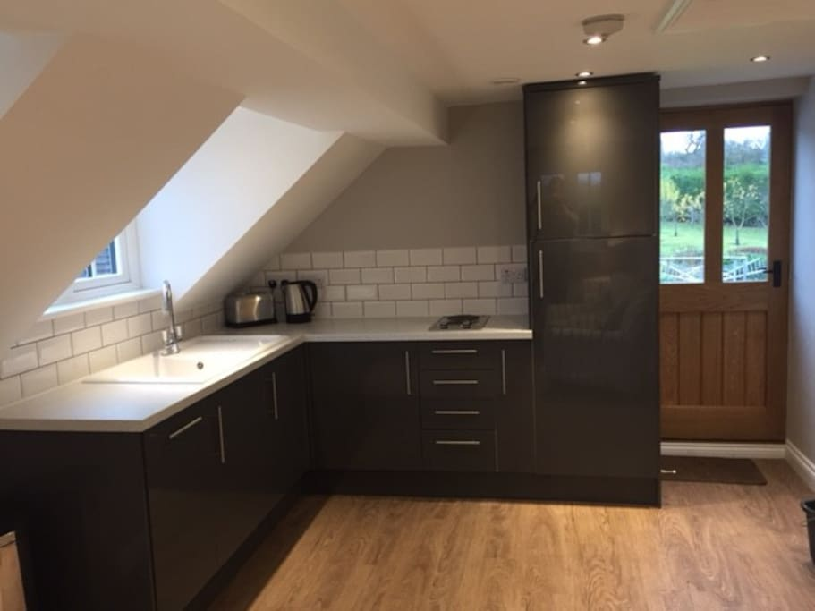 Modern kitchen area with small dishwasher, fridge and hob. The kitchen is well equipped.