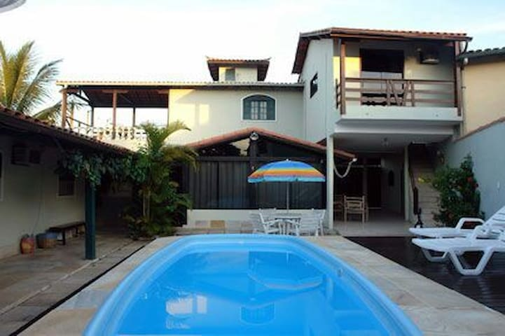 Imagem de frente da pousada com piscina e um espaço pra descansar.