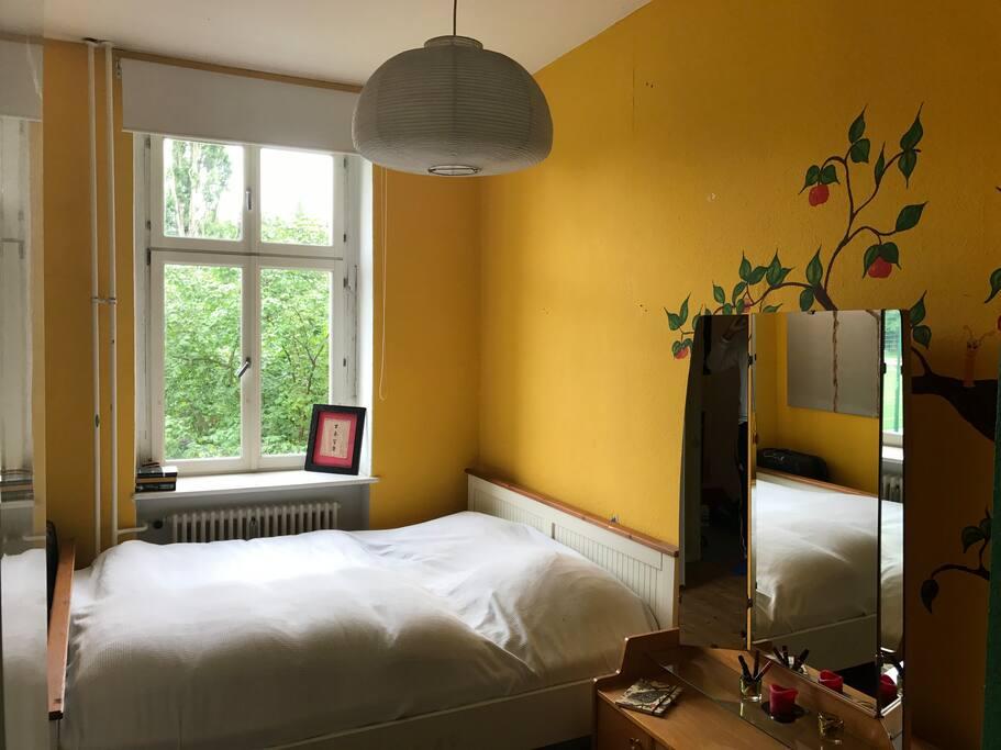 Schlafzimmer mit Fenster ins Grüne.