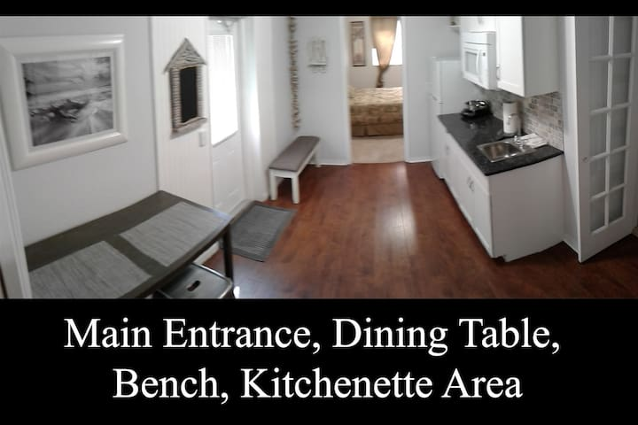 Inside Main Entrance Area with Bistro Table, Bench and Kitchenette. (angle 1)