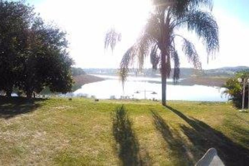 Área de piscina, gramado e churrasqueira todas integradas com a vista para a represa