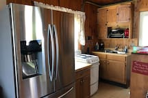Kitchen with dishes, silverware, pots and pans, stove, microwave, and refrigerator.