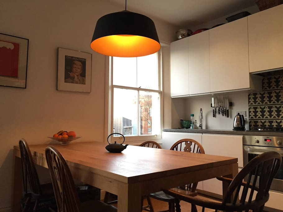 Large dining table and sunlit kitchen