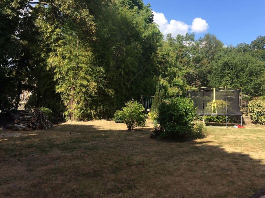 Jardin avec barbecue, trampoline, balançoire et petite piscine.