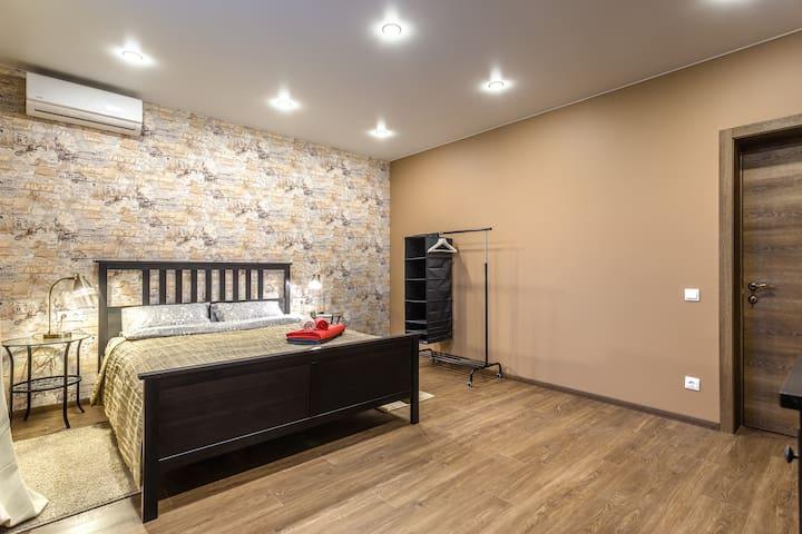 Первая спальня с кроватью шириной 160 см, стеклянными прикроватными столиками и светильниками, вешалкой для вашей одежды, кондиционером. Авторские обои от петербургского дизайнера - с музыкальным сюрпризом)