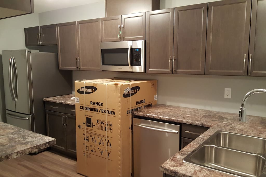 Kitchen with refrigerator, stove (still in the box). microwave, dishwasher, breakfast nook