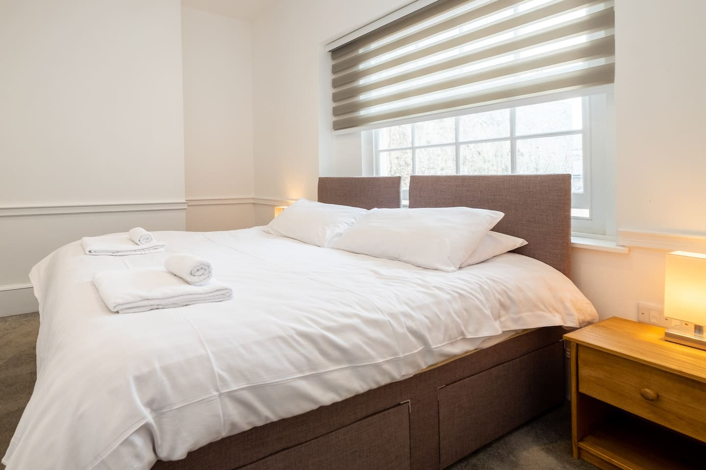 The bedroom has a double bed made up with fresh white linen and towels