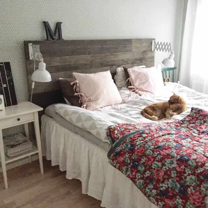 Master bedroom med dubbelsäng och vacker utsikt över skogen.