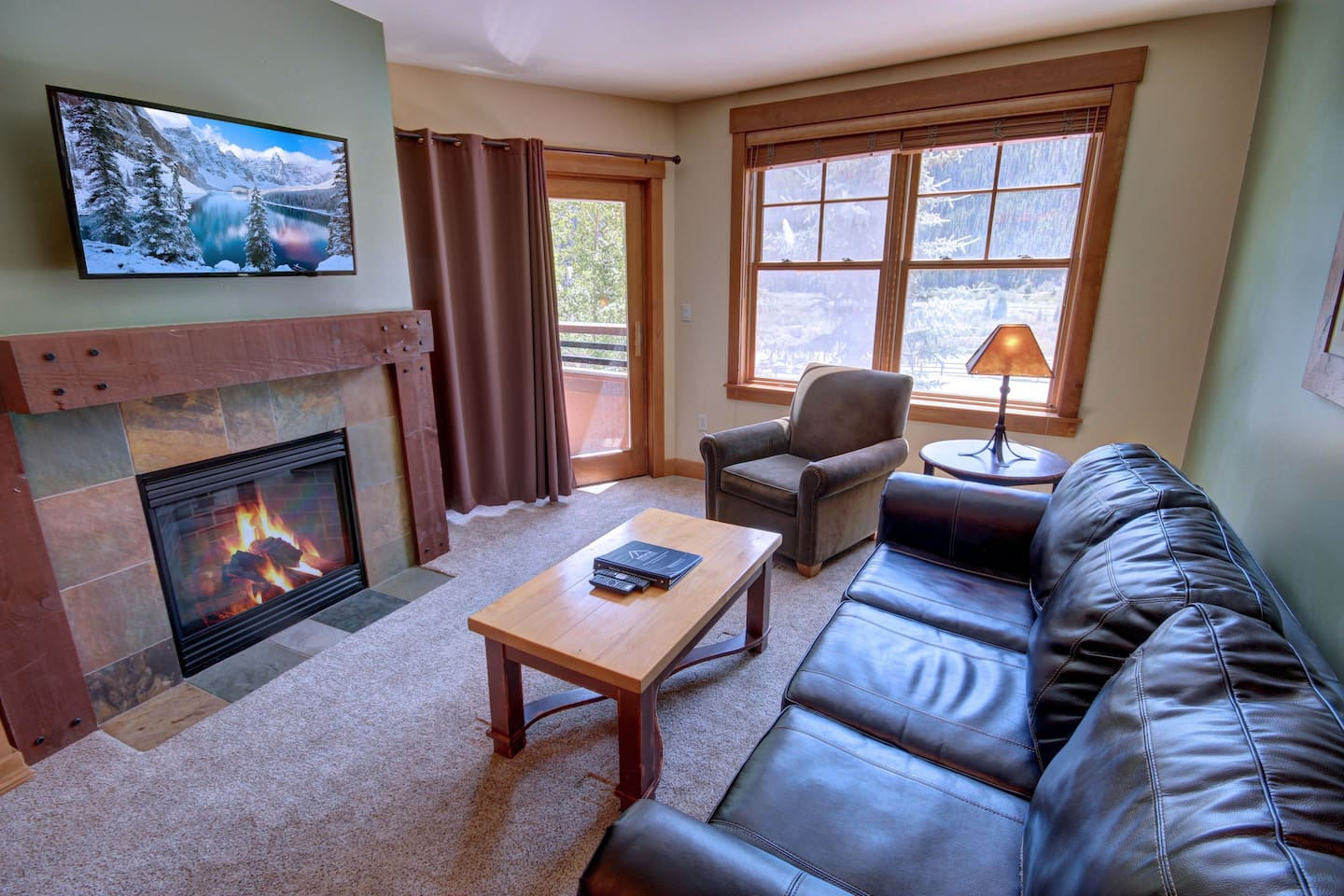 A living room with lots of natural lighting and a TV and fireplace for cold days