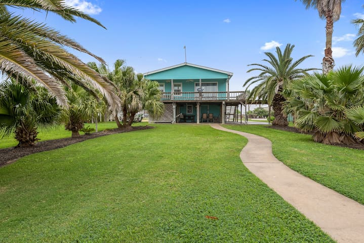 Well manicured yard with mature palms lining the yard on both sides for privacy and a relaxing coastal feeling! This house has the best yard on Caney Creek!
