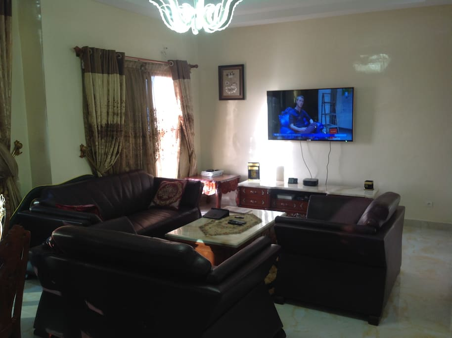 Spacious luxurious living room with real leather furniture, marble flooring, high ceiling and crystal chandeliers.