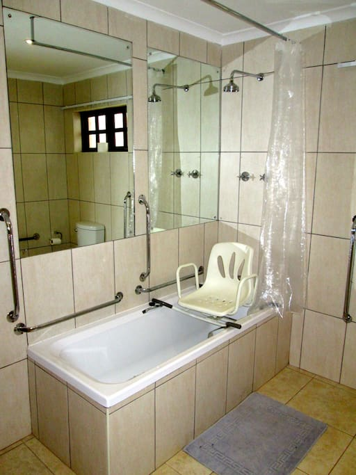 The en suite bathroom is fitted with a bath shower unit  and a portable swivel bath chair.