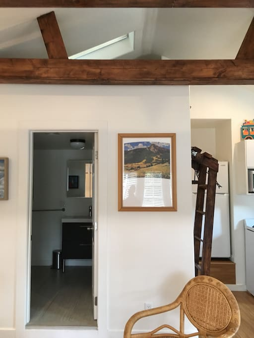 View from the entrance: bathroom and ladder from the kitchenette to the sleeping loft with queen-sized futon mattress; dual sky lights provide plenty of natural light and fresh airflow when opened, and can be closed/covered with blinds on hotter sunny days
