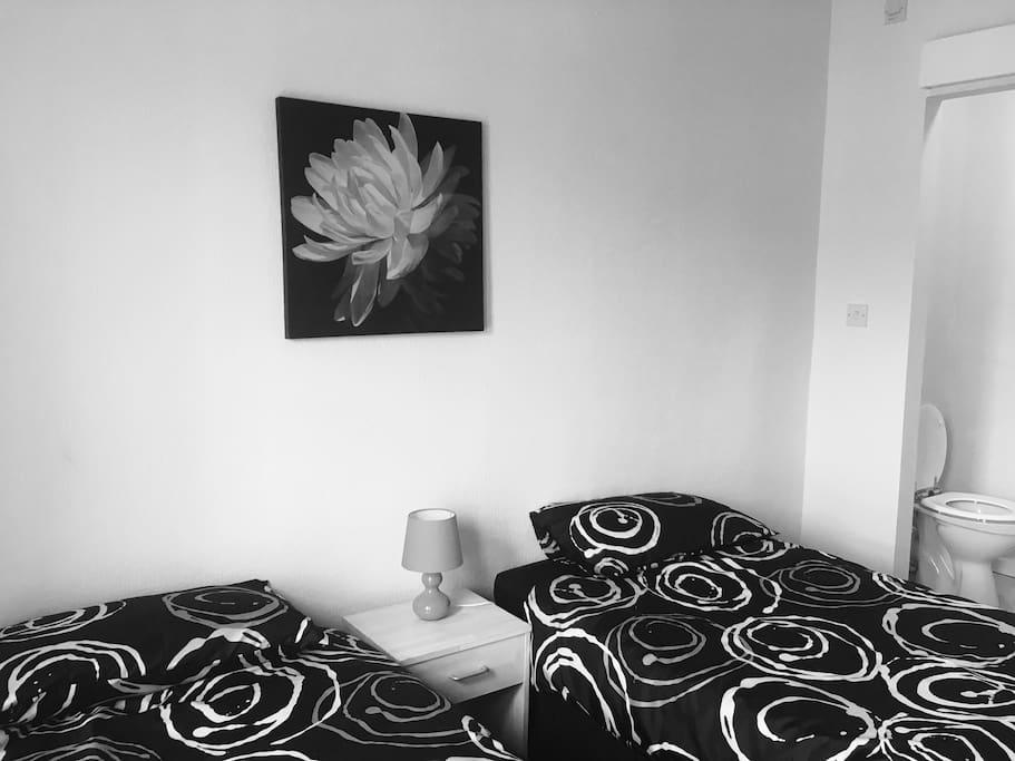 Twin Bedroom with En Suite facilities. Wardrobe, bedside table & lamp. TV & WiFi.