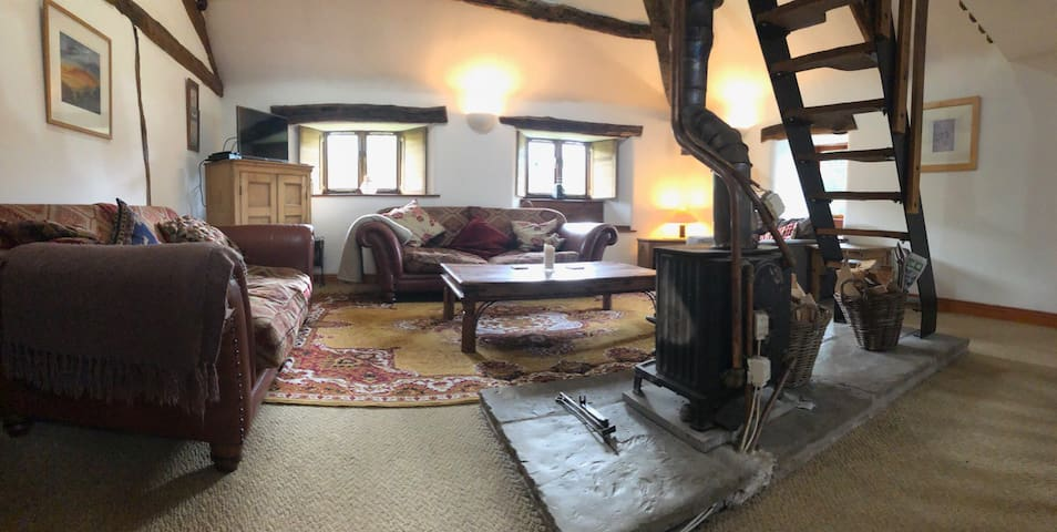 Living room , Two massive sofas and an easy chair around a large coffee table with fireplace.Windows look out onto garden and farmland beyond.