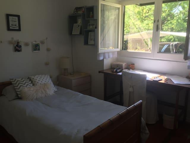Segundo dormitorio con una cama individual y cama en carro abajo, placar y escritorio con vista al jardín.
