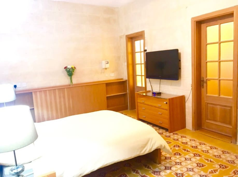 Large double bedroom with ensuite bathroom. traditional Maltese floor tiles and large flatscreen TV