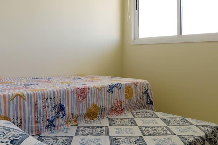 Quarto social com duas camas de solteiro e vista para as montanhas