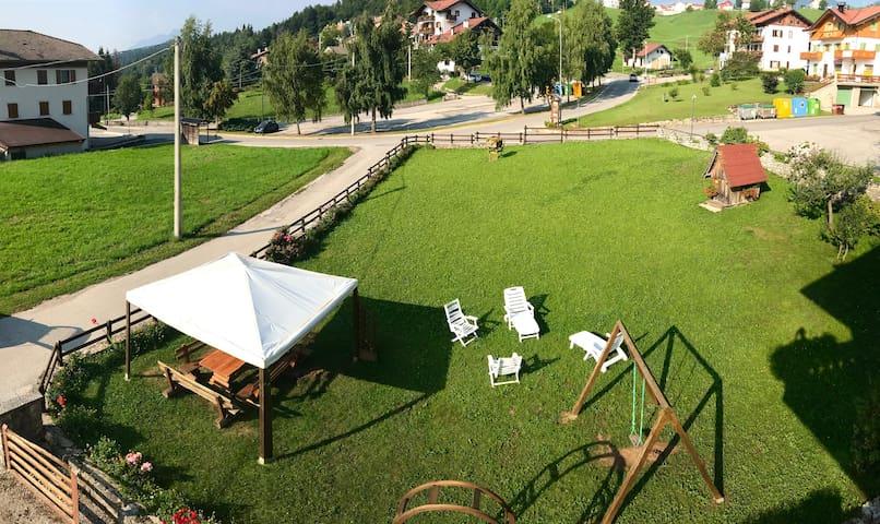 Vista del giardino estivo con gazebo e lettini