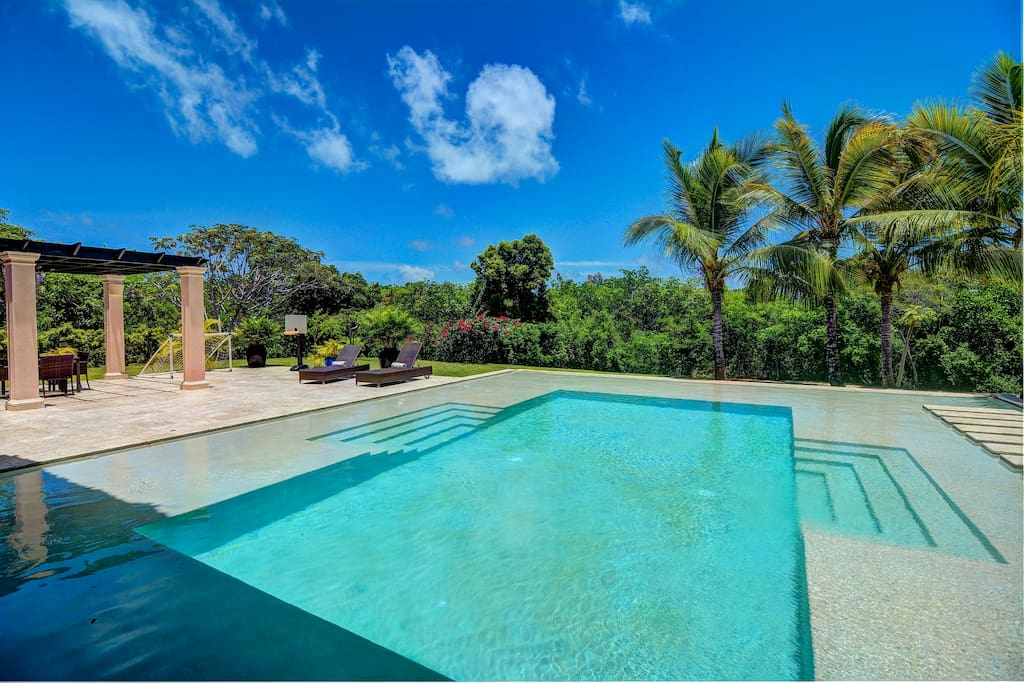Crystal blue infinity pool and tropical greenery beyond