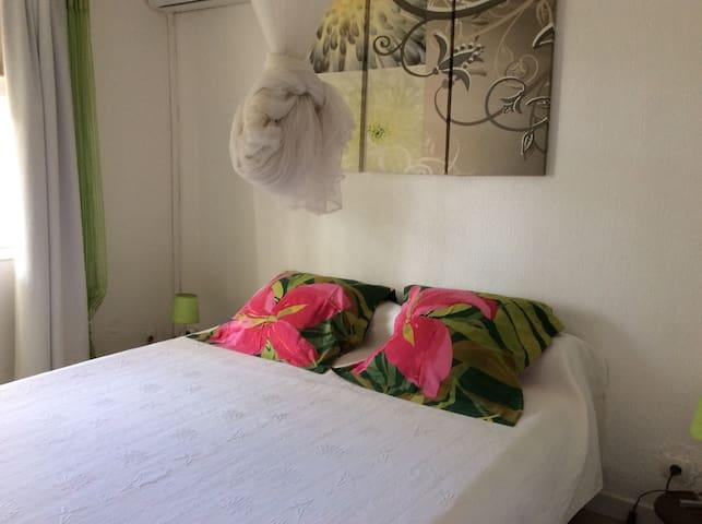 Chambre climatisée avec lit en 1,60m avec sur matelas et placard avec miroir.