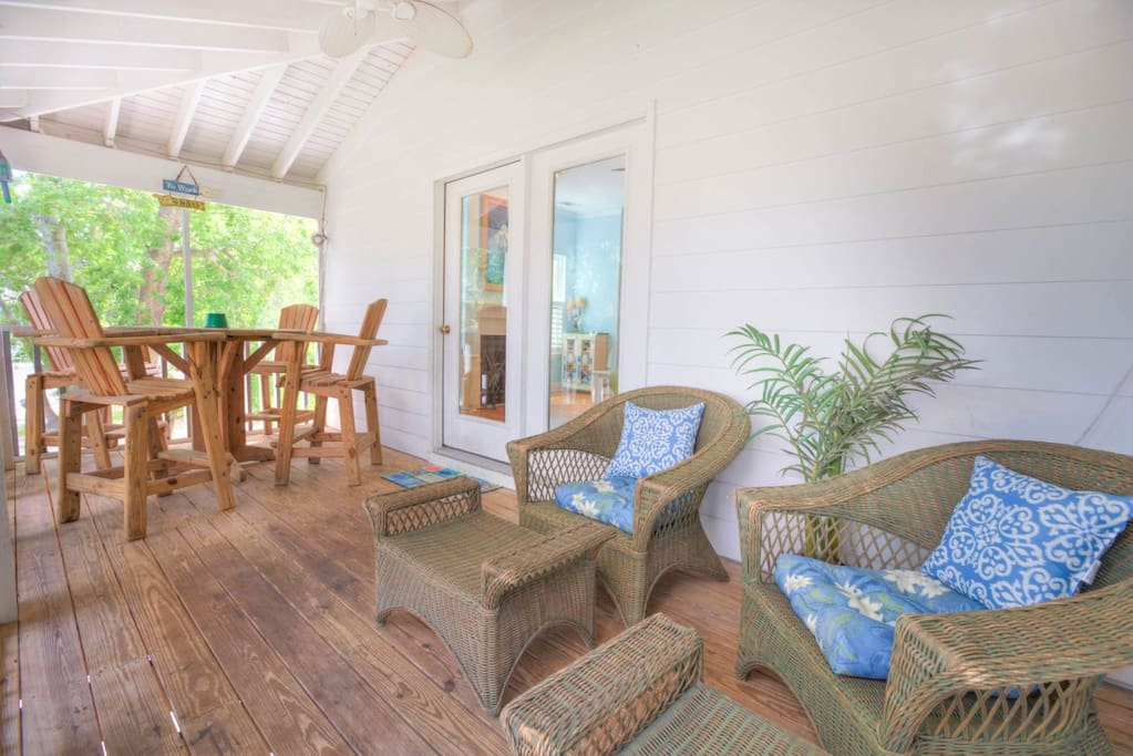 Large screened balcony area with bar height adirondack and comfortable wicker lounge chairs.