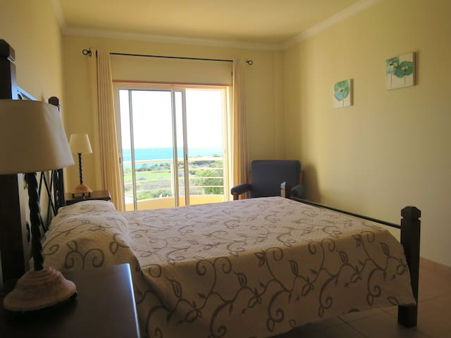 Bedroom 1 has double bed, fitted wardrobe and small veranda with sea and pool views