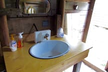 Clean, airy Privy with wash basin.