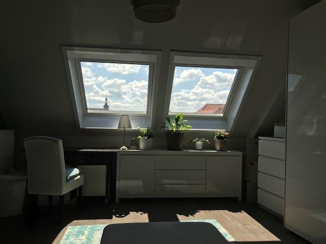 Schlafzimmer mit Blick über die Dächer und Himmel