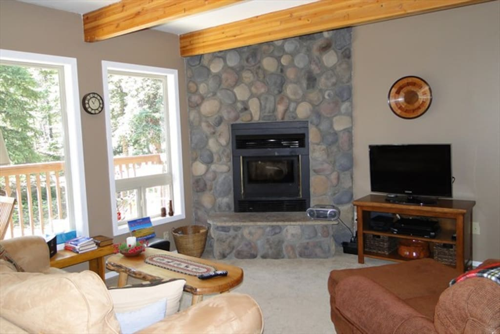 The living area has a stone wood burning fireplace.