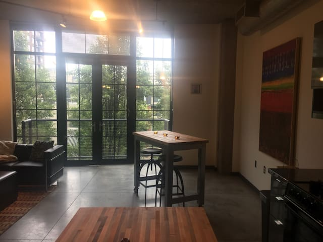View form kitchen to dining space and balcony. There are 2 2x4 tables on wheels that can be configured differently to serve as a 2x8, or 4x4 table as well.